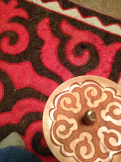 Spanish Peacock Mongolian themed laser engraved top whorl spindle and Kazakh shyrdak rug.